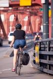 Le donne in breve guida la bicicletta con la borsa sul ponte rosso dell'azienda agricola fotografie stock
