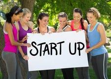Le donne in buona salute adatte che tengono il cartello che legge cominciano su Immagini Stock Libere da Diritti
