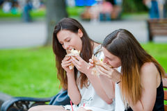 Le donne caucasiche mangia il panino degli alimenti a rapida preparazione dell'hamburger sulla via all'aperto Ragazze attive affa Fotografia Stock