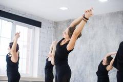 Le donne che fanno il saluto del sole di yoga posano all'interno allo studio di yoga Immagini Stock