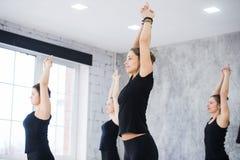 Le donne che fanno il saluto del sole di yoga posano all'interno allo studio di yoga Immagine Stock