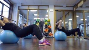 Le donne che gli atleti oscillano sulle palle premono su addestramento di forma fisica nella palestra stock footage