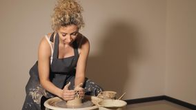 Le donne che lavorano al ` s del vasaio spingono Le mani scolpisce una tazza dal vaso di argilla stock footage