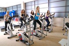 Le donne che risolvono sulla filatura bikes alla ginnastica Fotografia Stock