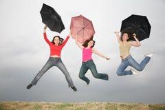 Le donne che saltano con il umbre Immagini Stock