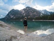 Le donne che stanno contro la vista stupefacente del lago Lago Braies con le montagne hanno riflesso nelle alpi delle dolomia del fotografia stock