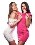 Le donne che tengono il lecca lecca rosa schioccano e che si divertono isolato insieme su bianco Immagini Stock