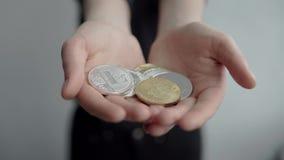 Le donne che tengono le monete cripto di ethereum e del litecoin del bitcoin di valuta in entrambe le mani e lo mostrano in camer video d archivio