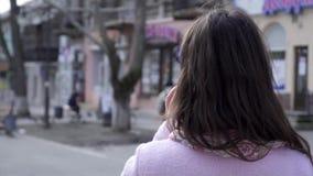 Le donne comunica sul telefono mentre camminano all'aperto chiuda su, retrovisione