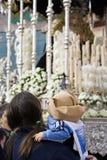 Le donne con un bambino nel suo arma l'abbigliamento di costalero in una processione della settimana santa fotografie stock libere da diritti