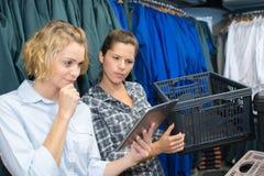 Le donne controlla le merci di disponibilità usando il cuscinetto di tocco Fotografie Stock