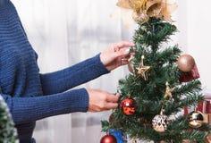 Le donne decorano l'albero di Natale durante il giorno di Natale ed il nuovo anno immagine stock