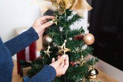 Le donne decorano l'albero di Natale durante il nuovo anno di giorno di Natale fotografie stock libere da diritti