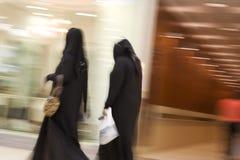 Le donne del Dubai UAE due si sono vestite in abayas ed abiti e sciarpe tradizionali del nero dei hijabs. immagine stock libera da diritti