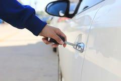 Le donne del primo piano passano la chiave dell'automobile della tenuta alla porta di automobile d'apertura o d'apertura immagine stock