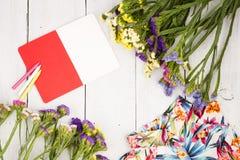 le donne dell'estate hanno messo con il vestito, i fiori variopinti, il blocco note e il penci fotografia stock