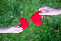 Le donne della mano inviano il cuore rosso e gli uomini della mano inviano il cuore rosso per i cuori di scambio, il doppio cuore fotografia stock