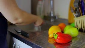 Le donne delle casalinghe delle mani lavano i peperoni sotto un rubinetto Destra dello scorrevole della macchina fotografica stock footage