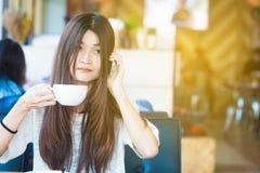 Le donne dello studente utilizzano lo smartphone in caffè alla biblioteca immagini stock libere da diritti