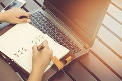 Le donne di affari che per mezzo del computer portatile e notano alcuni dati Immagini Stock Libere da Diritti
