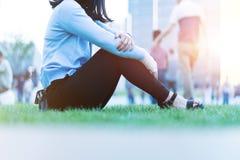 Le donne di dolore della mano del polso si siedono sull'erba verde nel campo da giuoco sul tramonto, concetto di stile di vita de immagine stock