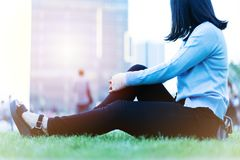 Le donne di dolore della mano del polso si siedono sull'erba verde nel campo da giuoco sul tramonto, concetto di stile di vita de immagini stock