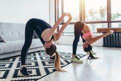Le donne di forma fisica appoggiano l'allungamento della formazione a casa La giovane ragazza esile fa la curvatura di andata Fotografia Stock Libera da Diritti