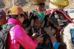 Le donne di Ladakhi esaminano la loro foto in camera del turista straniero immagine stock libera da diritti