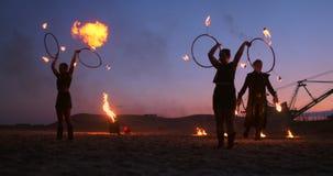 Le donne di manifestazione tre del fuoco in loro mani torcono le lance brucianti ed i fan nella sabbia con un uomo con due lancia stock footage
