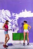 Le donne dipinge la parete bianca con il rullo di pittura porpora fotografia stock libera da diritti