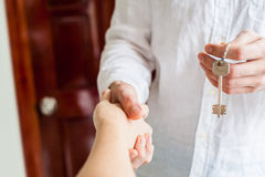 Le donne e l'uomo che stringono le mani delle mani soltanto da vedere e una chiave è sono dati sui precedenti di una porta di leg fotografia stock