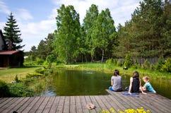 Le donne e la ragazza che si siedono da un villaggio alloggiano lo stagno fotografie stock