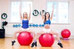 Le donne fanno l'allungamento dell'esercizio Fotografia Stock