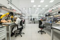Le donne fanno la saldatura delle componenti radiofoniche ai bordi elettronici Pianta per la produzione di attrezzatura elettroni Fotografia Stock
