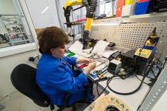 Le donne fanno la saldatura delle componenti radiofoniche ai bordi elettronici Pianta per la produzione di attrezzatura elettroni Immagine Stock
