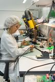 Le donne fanno la saldatura delle componenti radiofoniche ai bordi elettronici Pianta per la produzione di attrezzatura elettroni Fotografia Stock Libera da Diritti