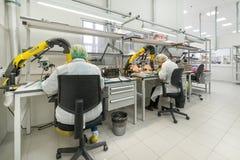 Le donne fanno la saldatura delle componenti radiofoniche ai bordi elettronici Pianta per la produzione di attrezzatura elettroni Immagini Stock