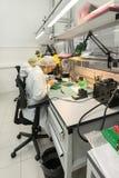 Le donne fanno la saldatura delle componenti radiofoniche ai bordi elettronici Pianta per la produzione di attrezzatura elettroni Fotografie Stock Libere da Diritti