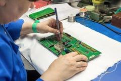 Le donne fanno la saldatura delle componenti radiofoniche ai bordi elettronici Pianta per la produzione di attrezzatura elettroni Immagini Stock Libere da Diritti