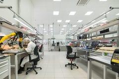 Le donne fanno la saldatura delle componenti radiofoniche ai bordi elettronici Pianta per la produzione di attrezzatura elettroni Fotografie Stock