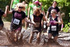 Le donne funzionano e spruzzano attraverso il pozzo del fango Immagine Stock