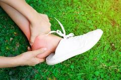 Le donne giudicano la sua caviglia torta causata da un incidente Dolore ritenente danneggiato della persona ed usando la tenuta d fotografia stock libera da diritti