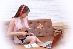 Le donne godono di una bevanda, ascoltano musica e giocano le ukulele fotografia stock