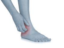 Le donne graffiano la caviglia itchy con la mano. Fotografie Stock