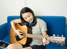 Le donne graziose giocano la chitarra acustica per il rilassamento a casa immagine stock libera da diritti