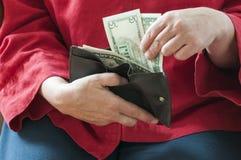 Le donne guarda in suo portafoglio Immagini Stock Libere da Diritti