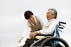 Le donne hanno assistito la sedia a rotelle Immagine Stock
