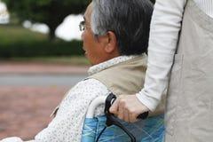 Le donne hanno assistito la sedia a rotelle fotografia stock libera da diritti