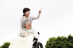 Le donne hanno assistito la sedia a rotelle Fotografia Stock