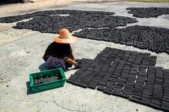Le donne hanno messo la barra del pacchetto del carbone fatta dalle coperture della noce di cocco sul pavimento fotografia stock libera da diritti